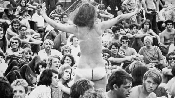 A naked woman stands up in the crowd during the 1969 Woodstock festival in Bethel, N.Y.