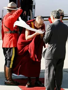 The Dalai Lama offers a white scarf, called a kata, as he is greeted by Senator Con Di Nino, co-chairman of the Parliamentary Friends of Tibet, upon his arrival at the Ottawa International Airport on Sunday.