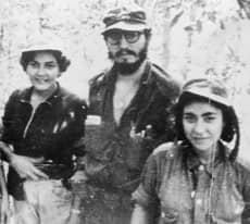 Cuban rebel leader Fidel Castro poses with two unidentified women who joined the rebel forces as nurses in this Feb. 6, 1958, file photo.
