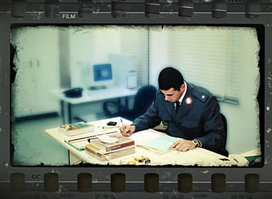 Capt. Eid, at work at his ISF office, from a videotape his brother made. A computer specialist, he had the kind of mind that could see intricate patterns. (Courtesy Eid family/CBC)