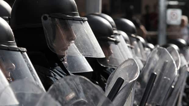 Police in riot gear stand guard in front of activists during a protest ahead of the G20 summit in downtown Toronto on June 25, 2010.