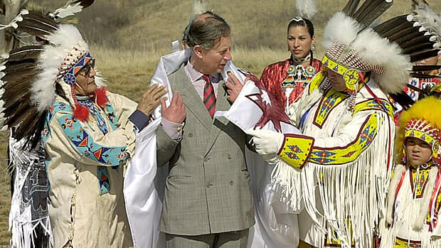 Prince Charles participates in a Cree naming ceremony with elder Gordon Oakes (left) and Chief Perry Bellegarde in April 2001. His Cree name is Kisikawpisim Kamiyowahpahmikoot (The sun watches over him in a good way.