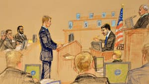 Khadr listens to witness Dr. Welner (right) respond to questioning by prosecution air force Capt. Chris Eason (centre) during his trial at Guantanamo Bay, Cuba