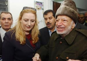 Yasser Arafat is led out of his compound in the West Bank by his wife, Suha Arafat, on Oct. 29, 2004 to board a helicopter bound for France in order to seek medical attention.