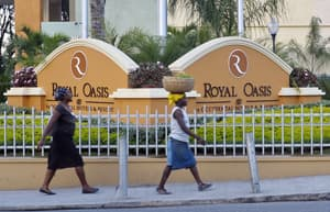 People walk in front of the new Royal Oasis Hotel in Port-au-Prince Dec. 13, 2012. The opening of the upscale hotel has ushered in a new phase in the country's post-earthquake reconstruction, while providing a sharp contrast to the plight of hundreds of thousands still homeless almost three years after the disaster.