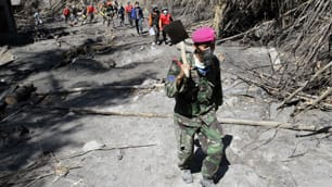 A soldier and volunteers walk as they search for victims of Mount Merapi's volcanic eruption at Glagaharjo village in Sleman, near Yogyakarta, on Monday.