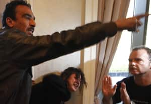 Al-Obaidi reacts as she is grabbed by a Libyan official, left, preventing members of the foreign media from reaching her.  As reporters gathered to hear her story, security guards grabbed al-Obaidi, bundled her into a car and drove her away. Several journalists were beaten during the scuffle.
