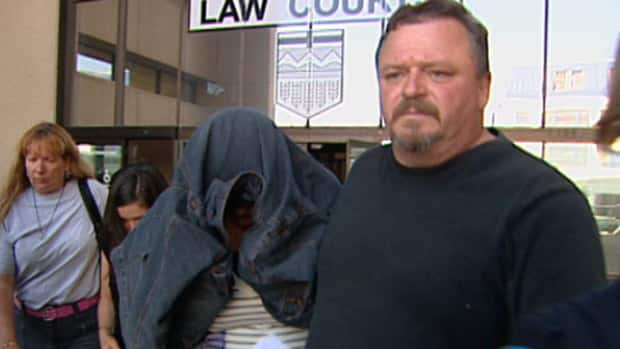 Katrina Effert is led out of the Edmonton Law Courts Friday by her father.