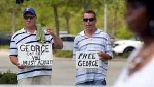 Patrick Woodburn, left, and William Memola hold signs supporting George Zimmerman in front of the Seminole County Courthouse.