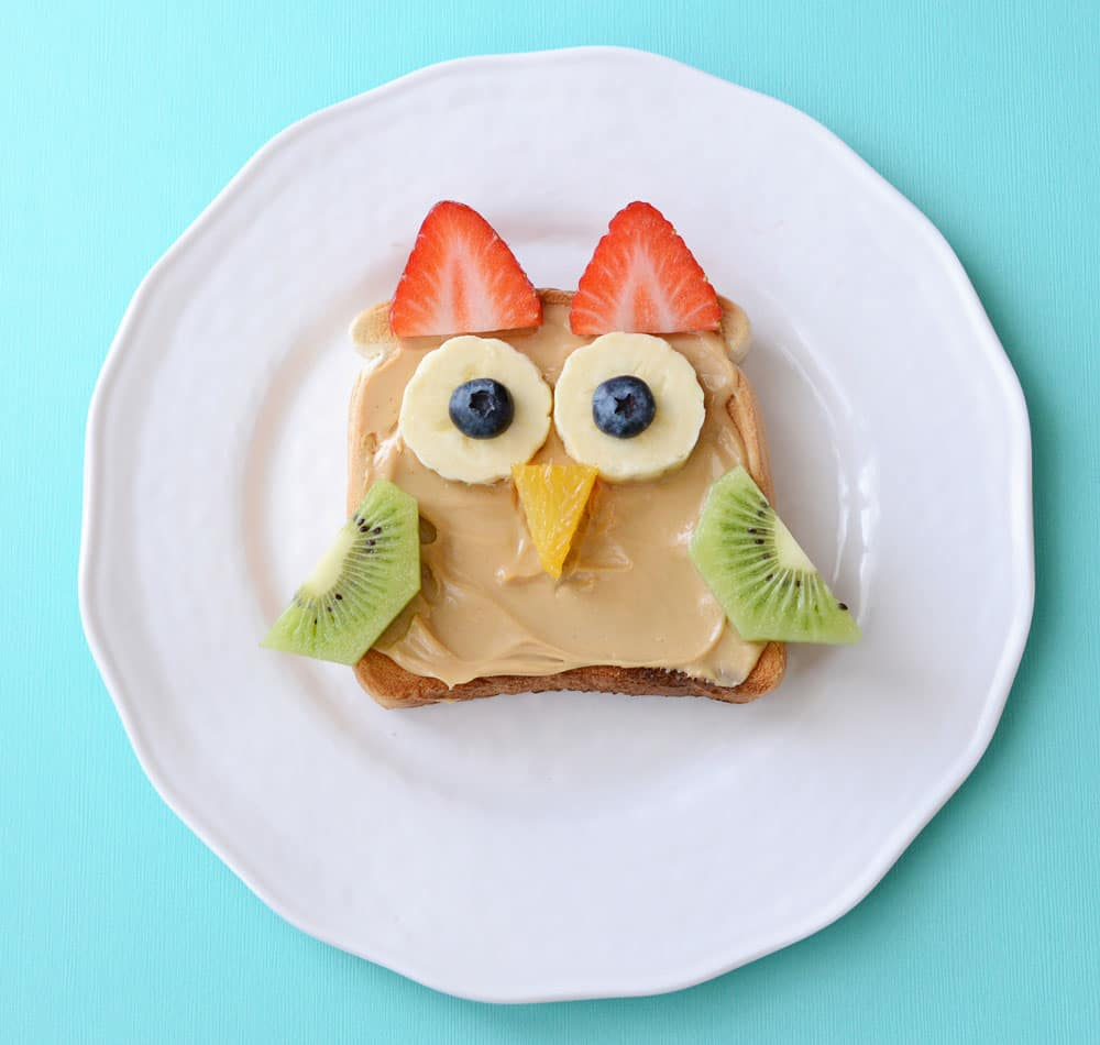A piece of toast coated with peanut butter, and with pieces of fresh fruit in the shape of an owl. Two slices of strawberry make the horns. Two slices of banana with blueberries on top make the eyes. A triangle of orange makes the beak and two halves of a slice of kiwi make the wings.