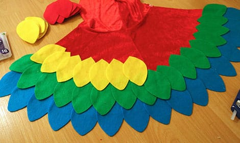 Two and a half rows of feathers have been glued onto the cape, which is laid out flat on the floor.