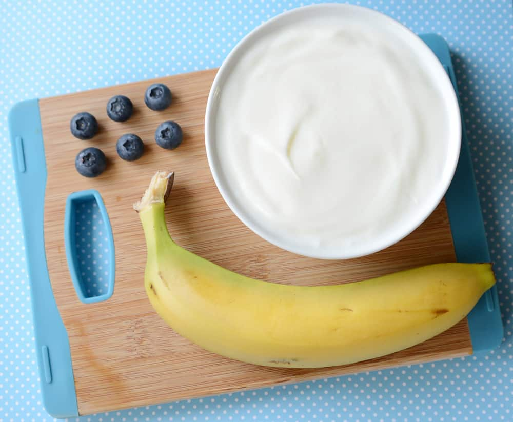 A bowl of yogurt, 6 blueberries and a banana.