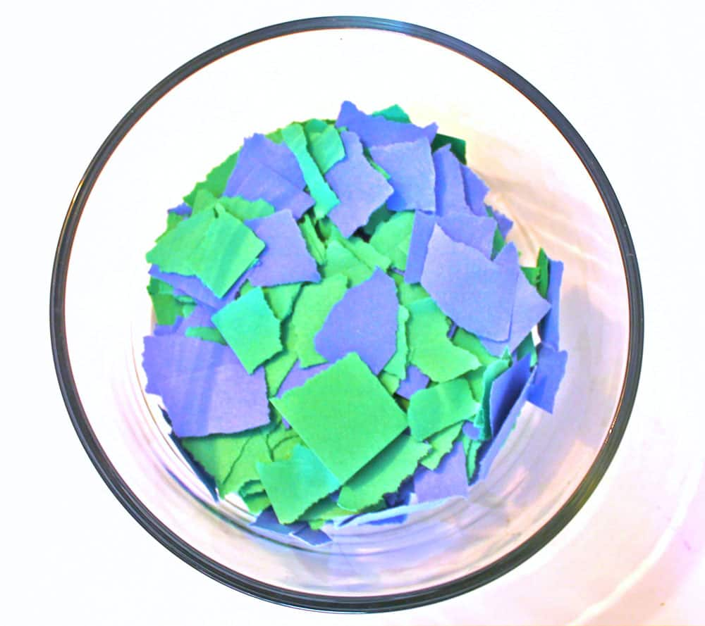 Bowl filled with torn bits of blue and green construction paper.