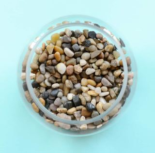 A small glass bowl filled with pebbles.