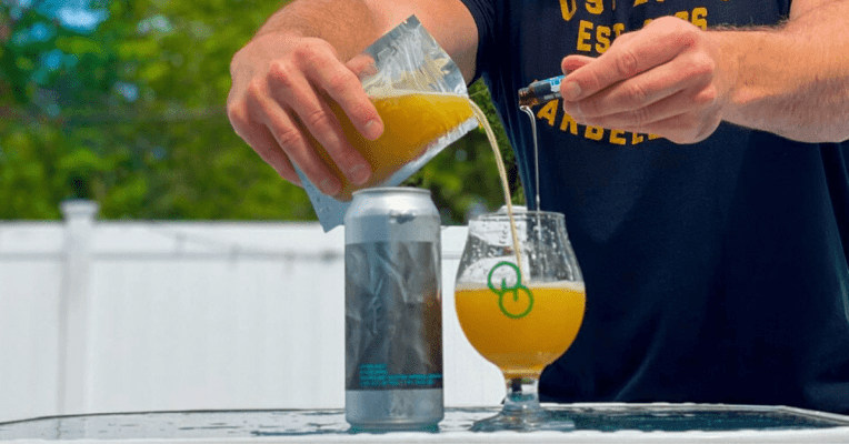 man pouring hemp beer into glass outside on a table