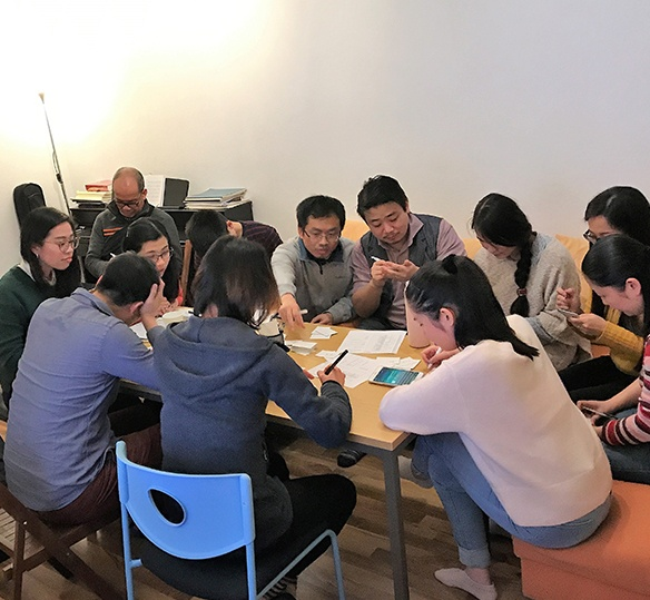 Photo of people sitting around a table writing