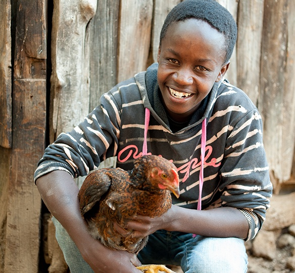 Photo of Kenyan man smiling with a chicken