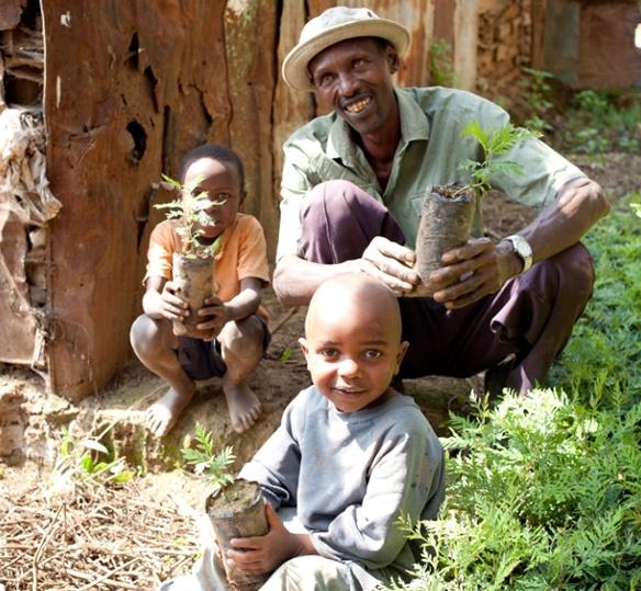 Photo of Kenyan family holding plants while smiling