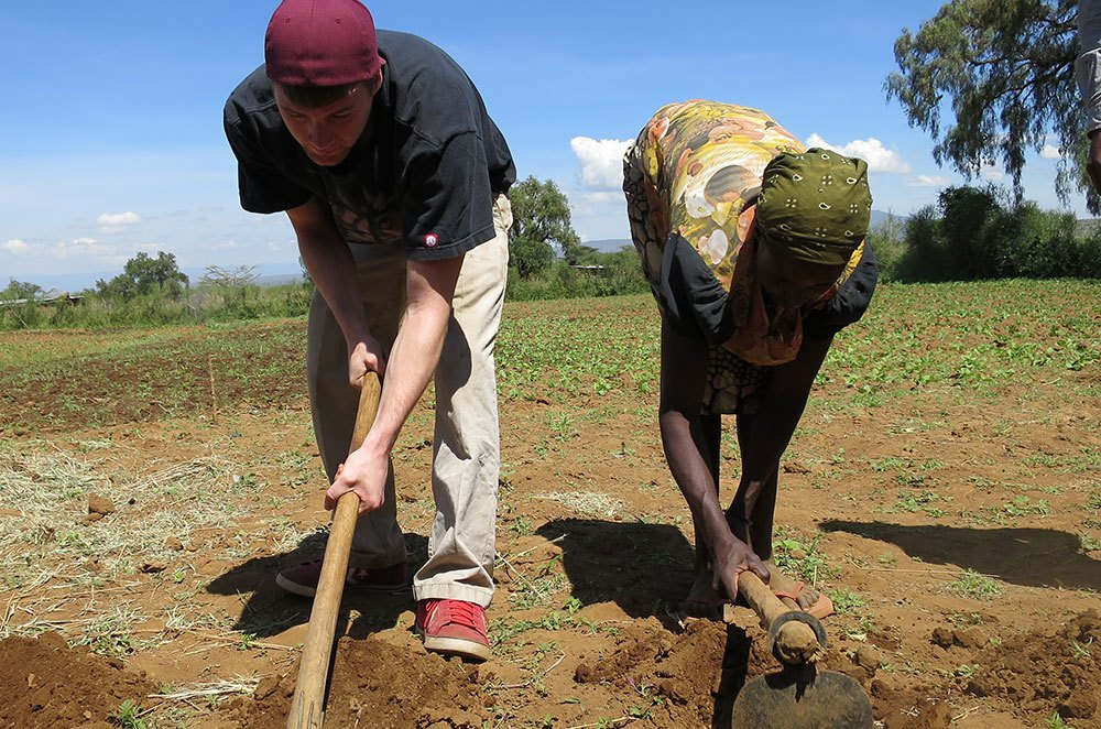 Photo of two people working together to till land