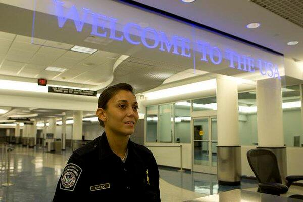 "A CBP officer stands under a sign that says ""Welcome to the USA"""
