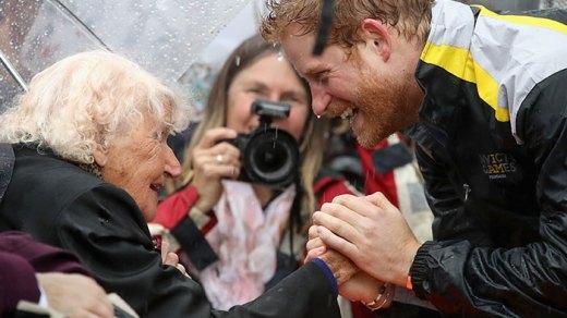Bajo la lluvia, el Príncipe Harry se acerca para saludar a señora de 97 años