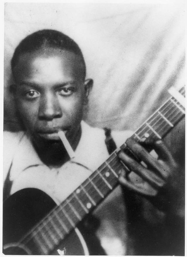 robert johnson smoking a cigaret and holding his guitar