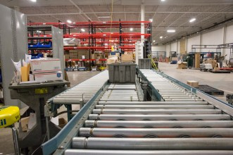 Totes flow on a lineshaft style powered-roller conveyor to our parcel shipping station.