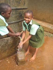 Two children get water from a well