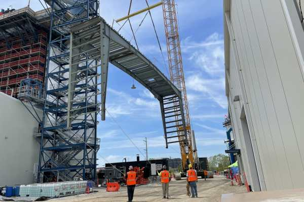 11Kiewit Power construction site, workers stand below raised frame