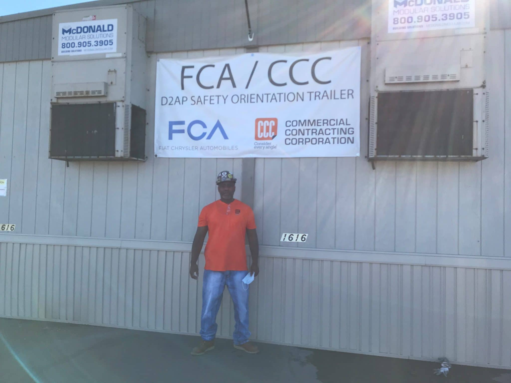 man in jeans and orange shirt below FCA/CCC sign