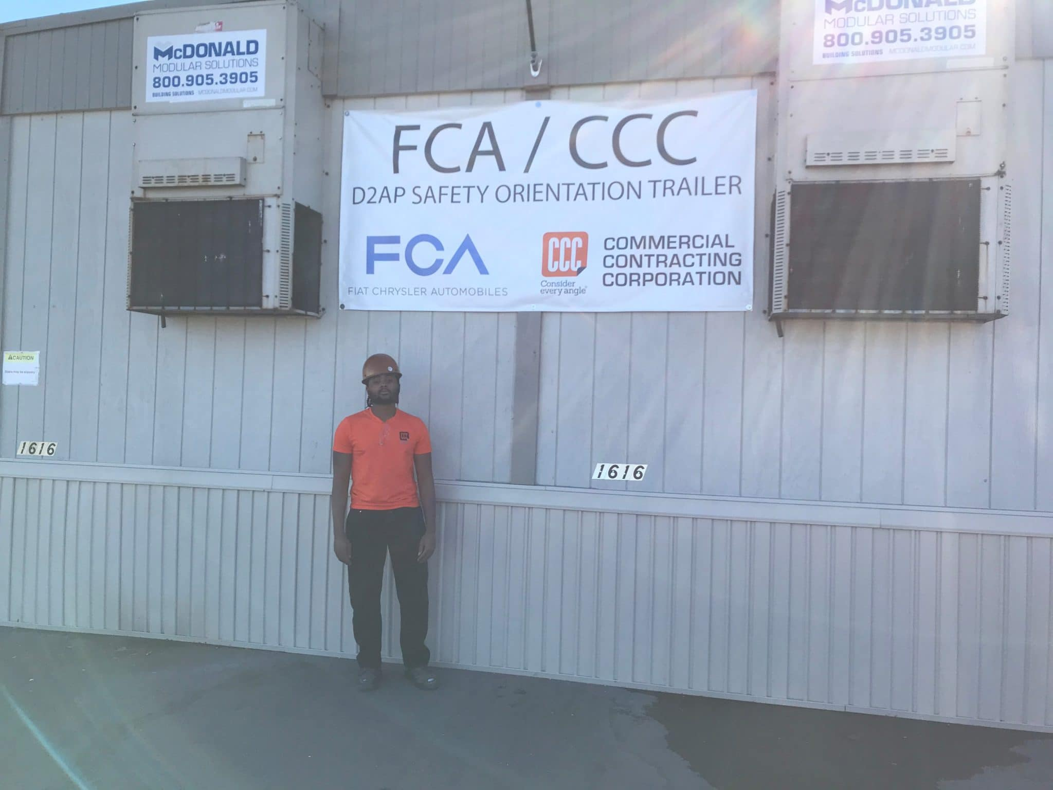 man in orange hard hat stands below FCA/CCC sign