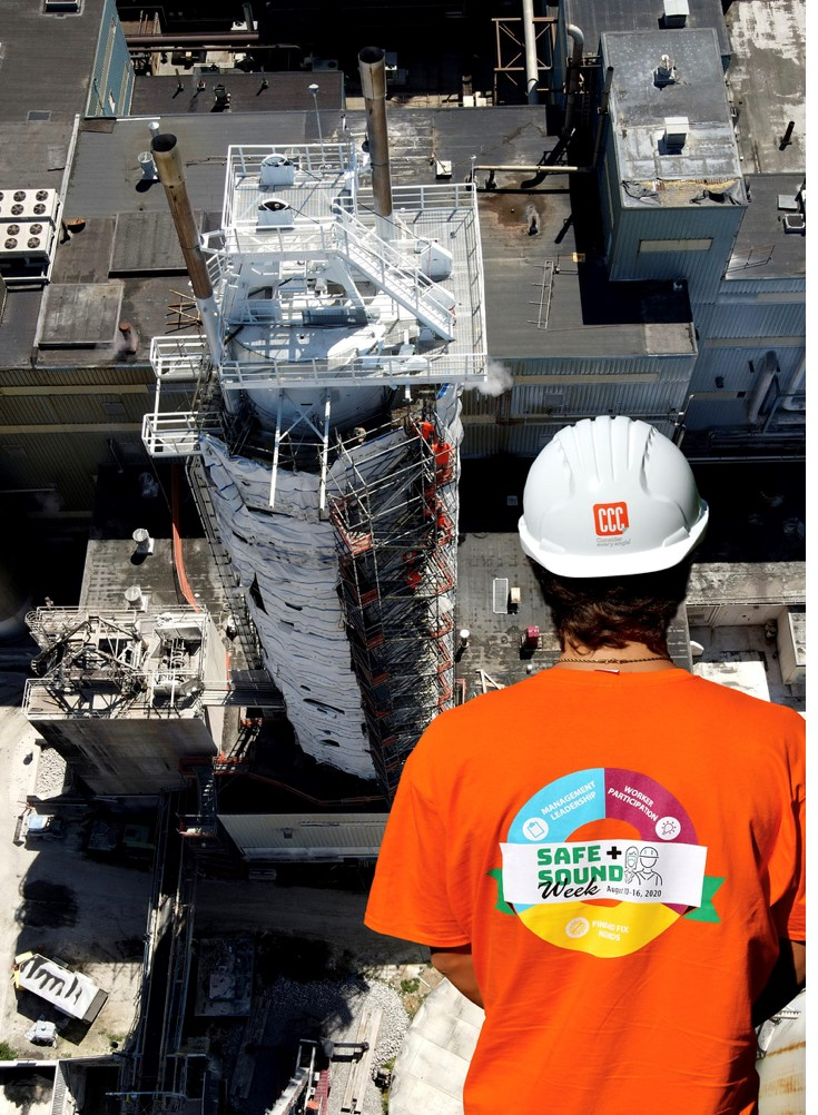 construction of tower with image of worker in orange shirt