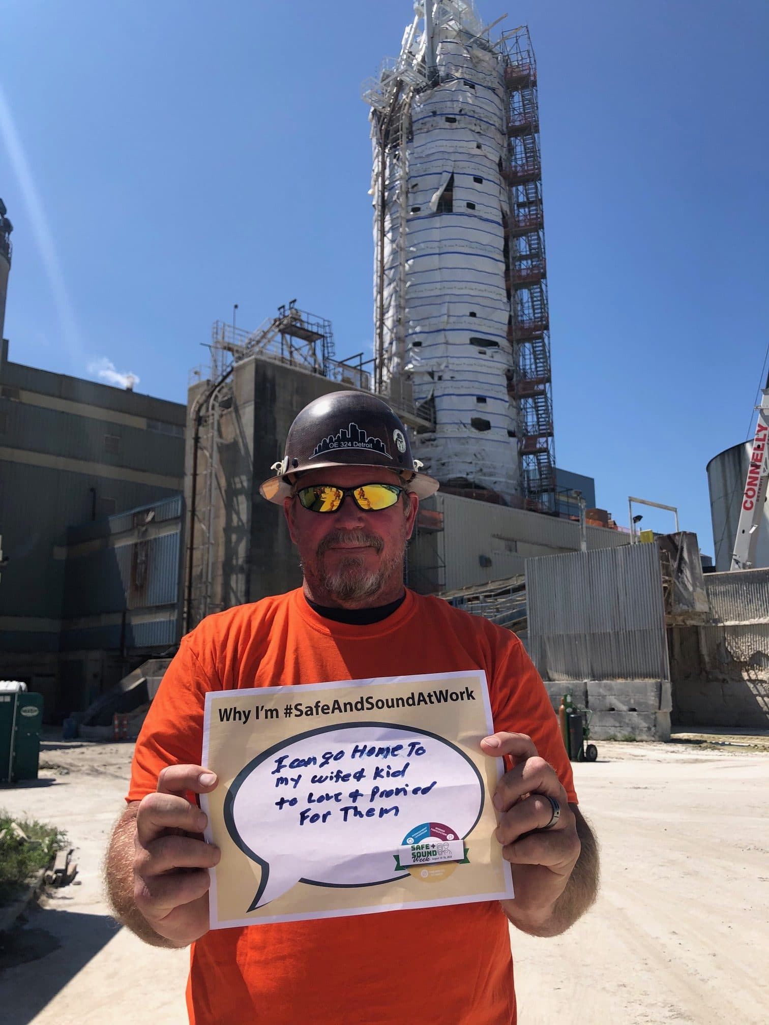 "construction worker holding ""love and provide"" sign"