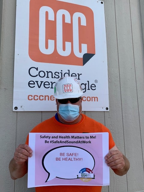"construction worker holding ""be healthy"" sign"