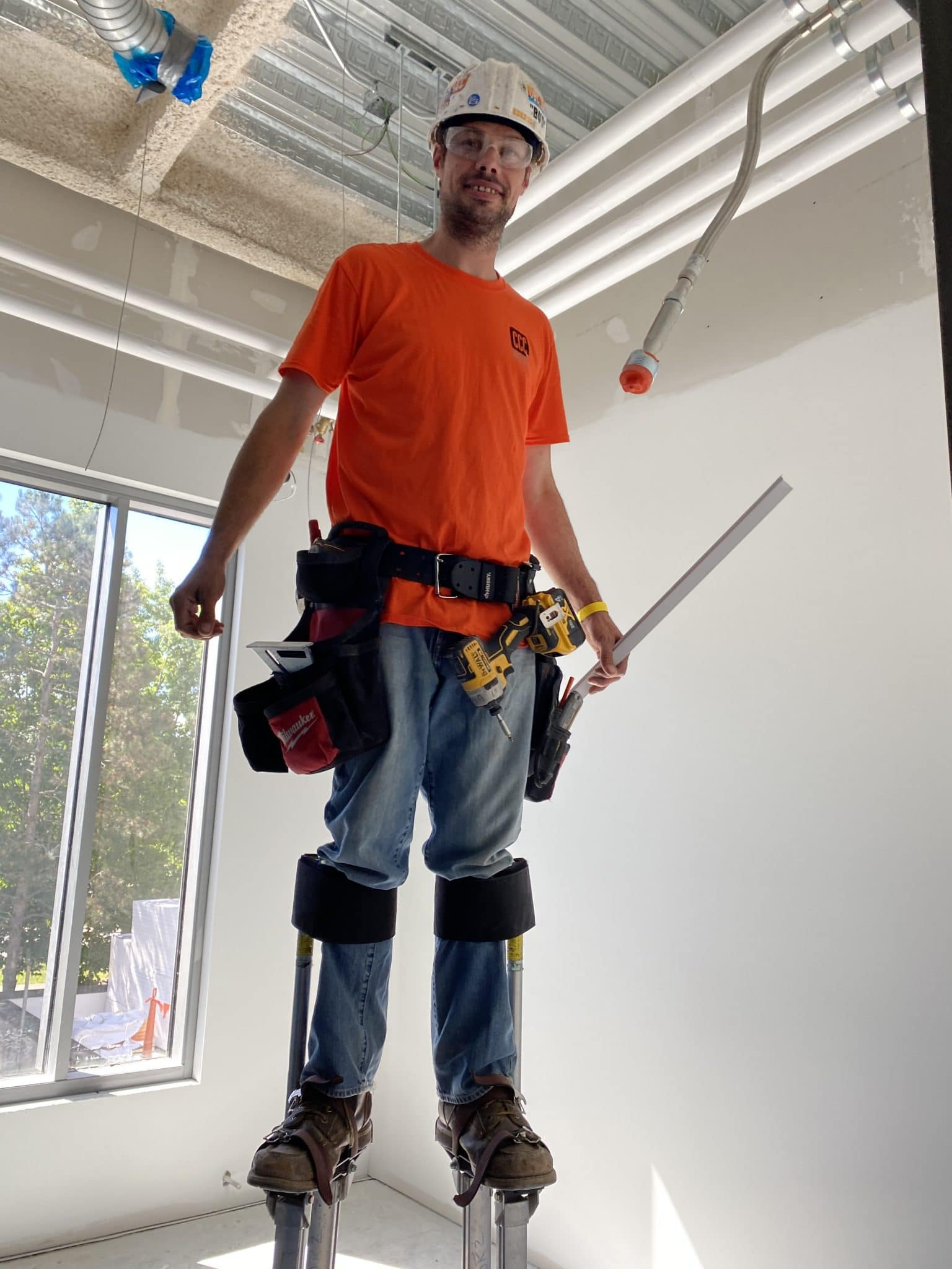 construction worker with orange shirt stands on stilts