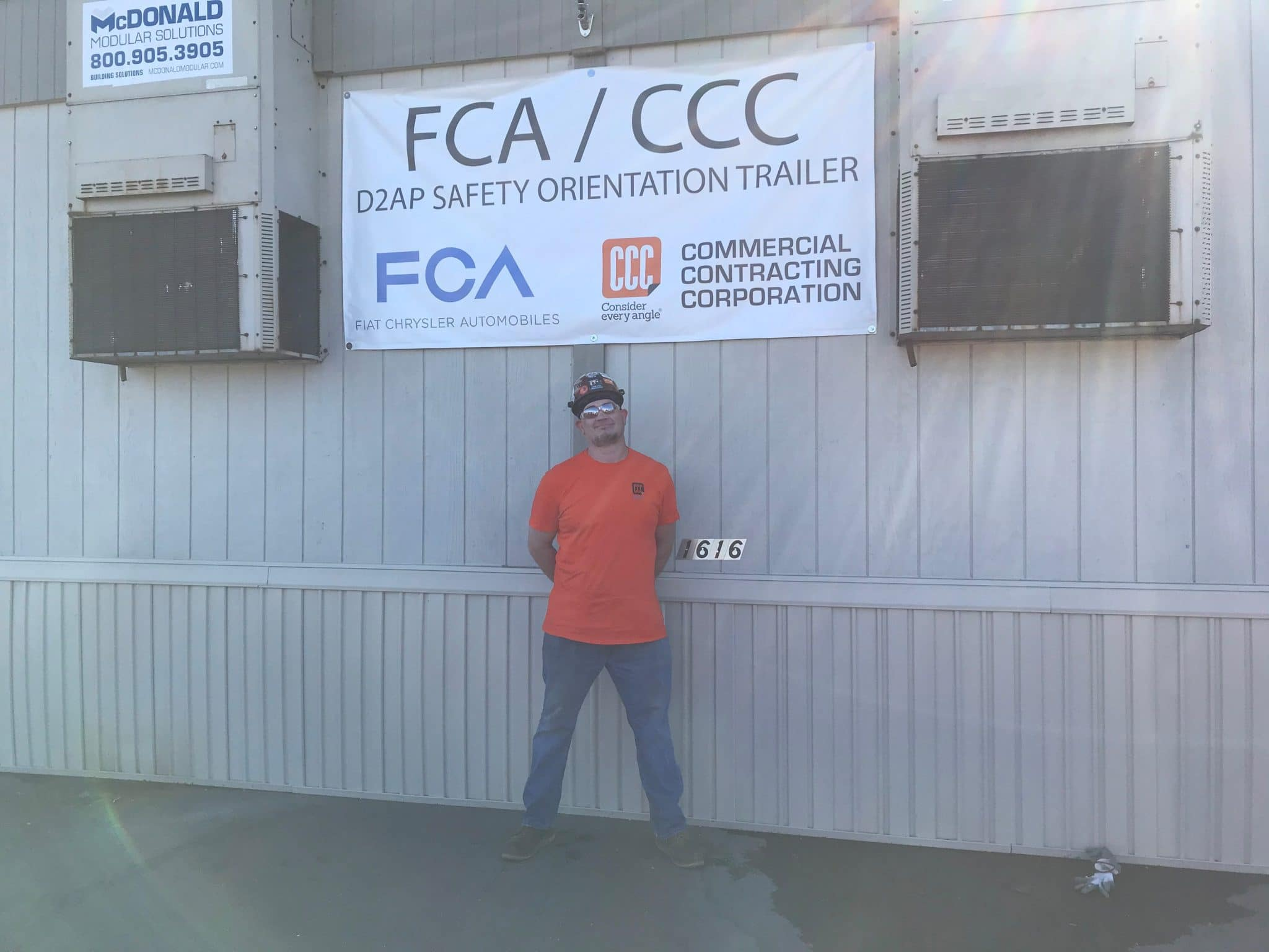 man with sunglasses stands below FCA/CCC sign