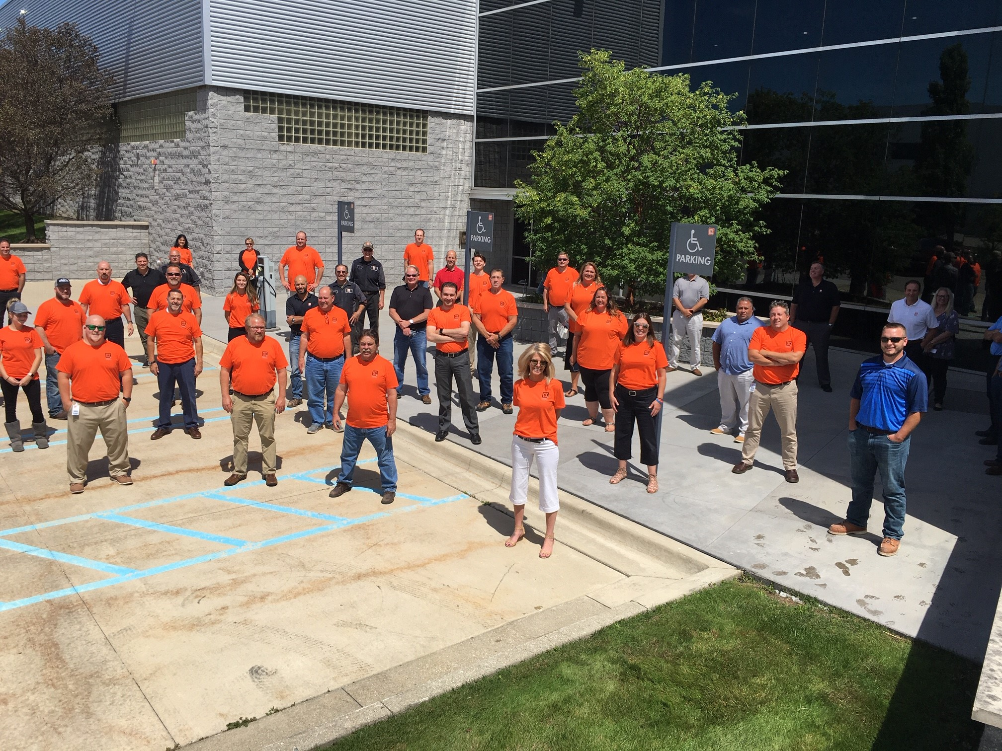 workers in orange shirts pose in front of office building