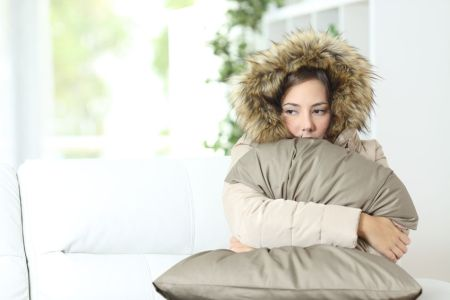 a woman holds her pillow because she needs heating repair in charleston