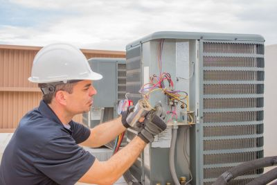technician preforming preventative maintenance on ac unit