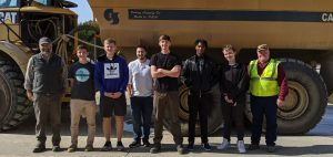 Students standing in front of a rock truck