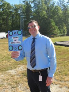 """Assistant Principal, Mr. White, holding """"Stomp out Bullying"""" sign."""