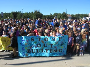 "Large group of LCES students holding ""Stomp out Bullying"" banner."