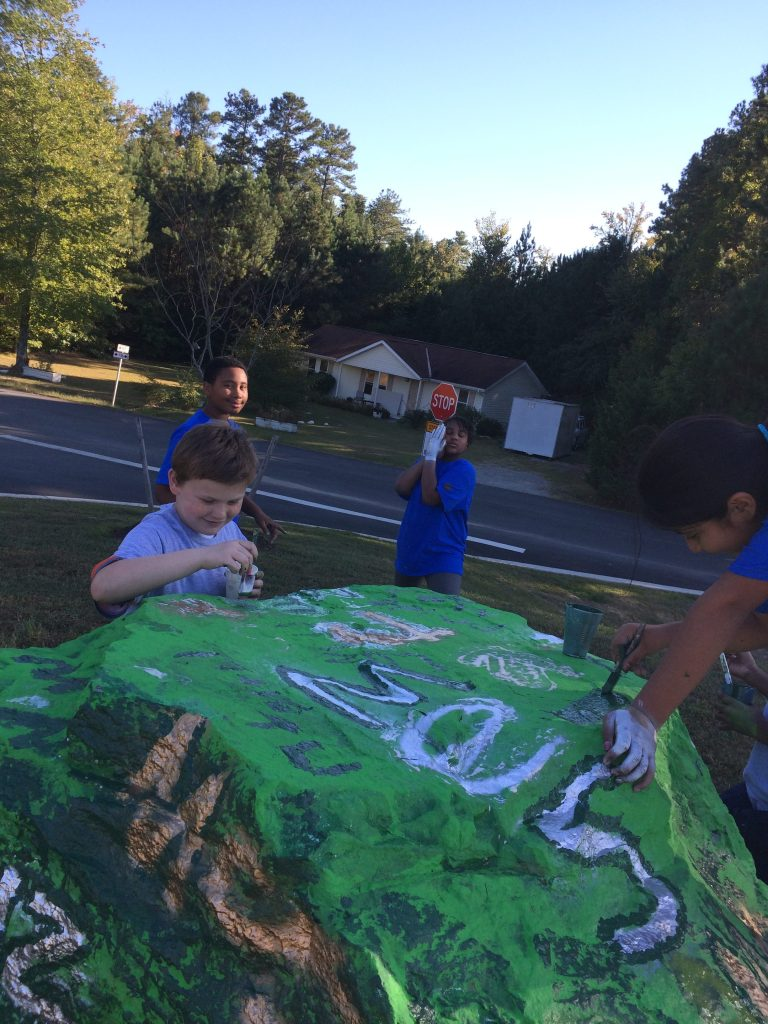 Students painting spirit rock