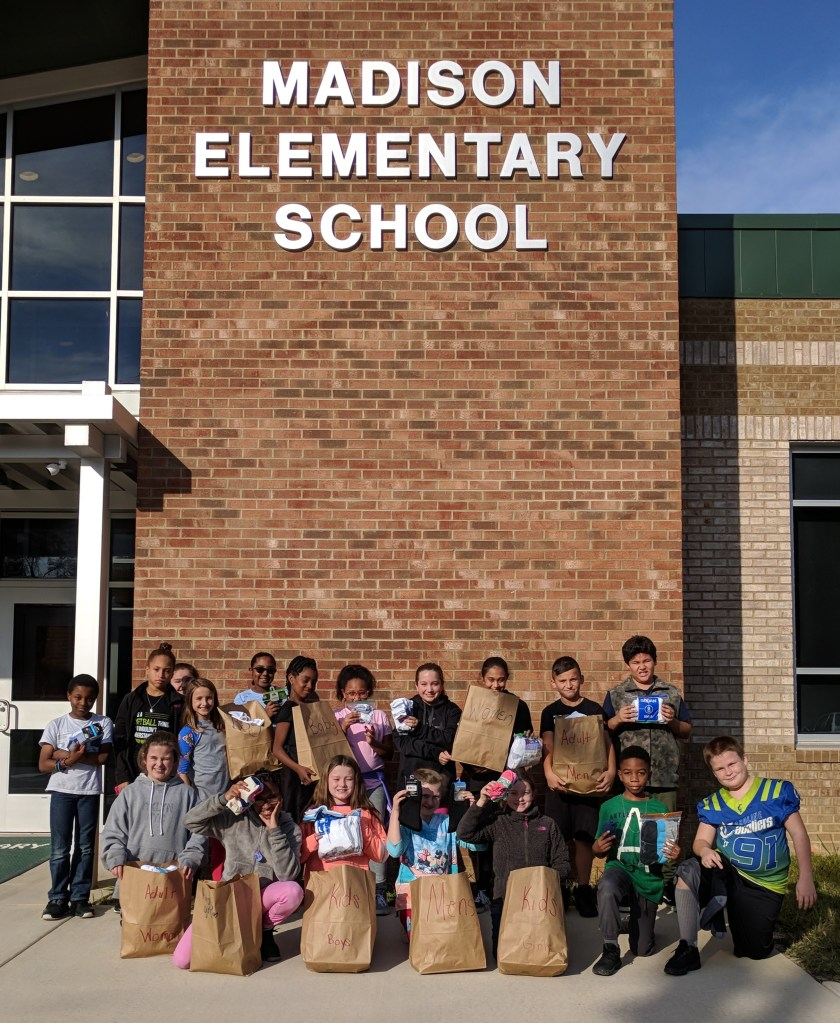 Students standing outside in front of the school with grocery bags of socks