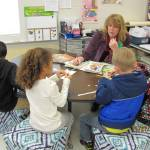 Teacher sitting with students at small group table