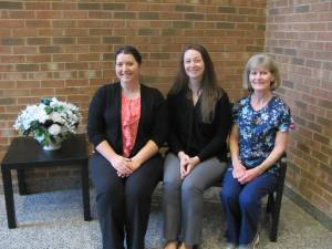 Mrs. Kidd, Mrs. Wik, and Mrs. Tinder sitting on a bench