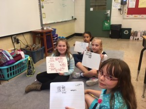 3rd grade students writing on dry erase boards