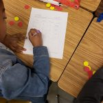 Third grader writing a fraction