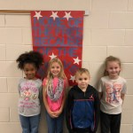 Students smiling with a veteran's day sign