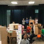 Students and teacher on stage at science fair